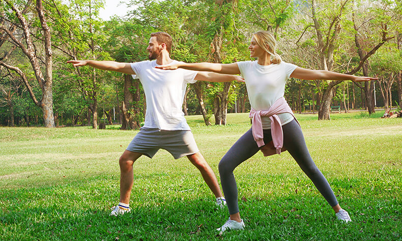 Couple doing yoga in park